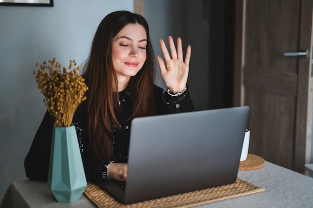 Retrato de uma jovem morena feliz sentada à mesa, olhando para a tela do laptop na videochamada e cumprimentando com acenos