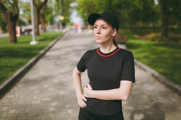 Retrato de uma jovem morena linda atlética de uniforme preto e boné em pé, descansando e olhando para o lado depois de correr, treinar no parque da cidade ao ar livre