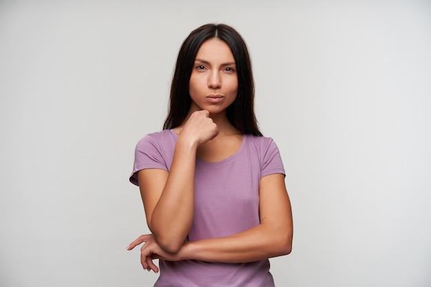 Retrato de uma jovem morena linda de olhos castanhos tocando suavemente seu hin com a mão levantada e olhando pensativamente com os lábios dobrados, isolado no branco em roupas casuais