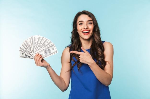 Retrato de uma jovem morena linda e animada de pé sobre o azul, mostrando notas de dinheiro e apontando o dedo