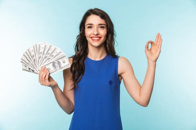 Retrato de uma jovem morena linda e animada em pé sobre o azul, mostrando notas de dinheiro, mostrando tudo bem
