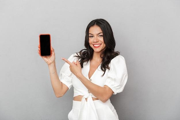 Retrato de uma jovem morena linda e animada, vestindo roupa de verão, em pé, isolado sobre uma parede cinza, mostrando a tela em branco do celular
