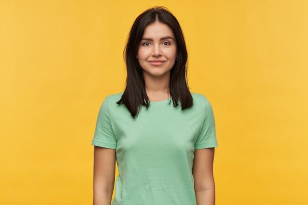 Retrato de uma jovem morena linda e feliz em uma camiseta de hortelã parece confiante sobre a parede amarela