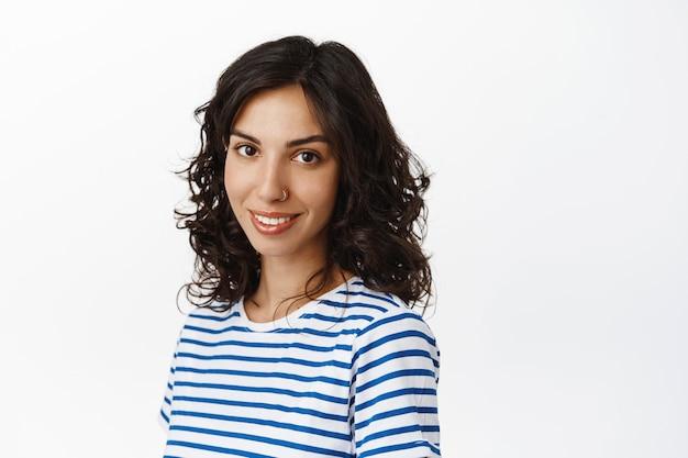Retrato de uma jovem morena moderna, sorrindo e olhando esperançosa, mostra o sorriso perfeito de dentes brancos, em pé em roupas casuais em branco.
