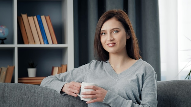 Retrato de uma jovem morena positiva segurando a xícara e olhando para a câmera sentada no sofá dentro de casa