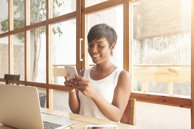 Retrato de uma jovem morena sentada em um café com um laptop
