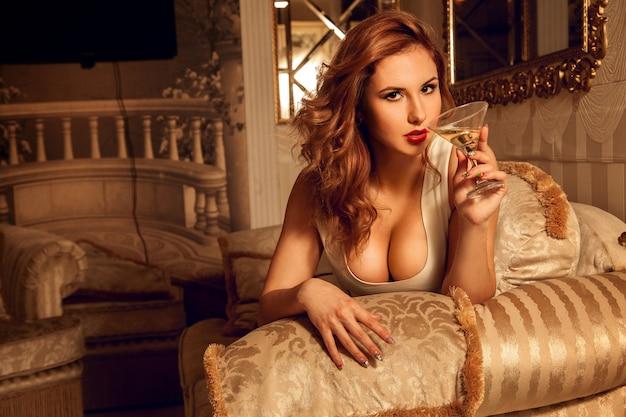 Retrato de uma jovem morena sexual com um copo de martini