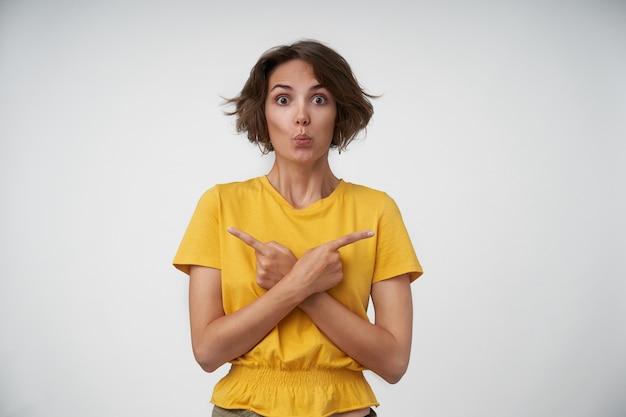 Retrato de uma jovem morena surpresa com o corte de cabelo curto, levantando as sobrancelhas e fechando os lábios em pé, mostrando-se em diferentes direções com o dedo indicador levantado