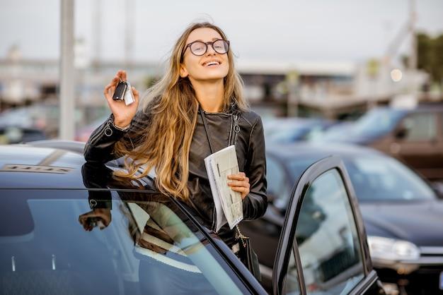 Retrato de uma jovem mostrando as chaves perto do carro alugado no estacionamento