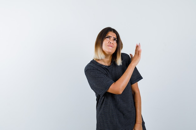Retrato de uma jovem mostrando gesto de parada em um vestido polo e olhando pensativa para a frente