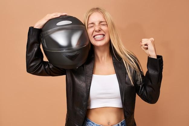Retrato de uma jovem motociclista alegre e radiante com aparelho dentário e cabelo longo e reto posando isolada em uma jaqueta de couro preta cerrando os punhos após vencer a corrida