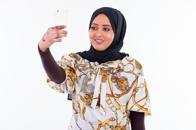 Retrato de uma jovem muçulmana africana usando um hijab isolado contra uma parede branca