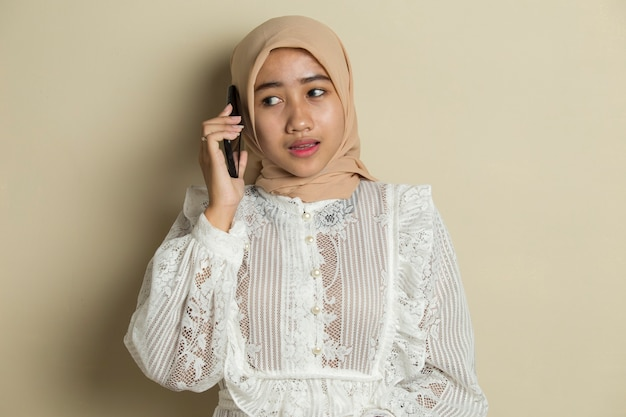 Retrato de uma jovem muçulmana asiática usando telefone celular