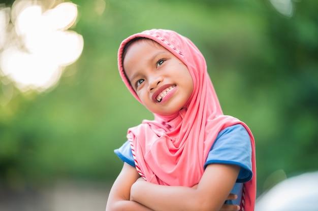 Retrato de uma jovem muçulmana, coberta com pano vermelho, sorrindo, feliz e copie o espaço