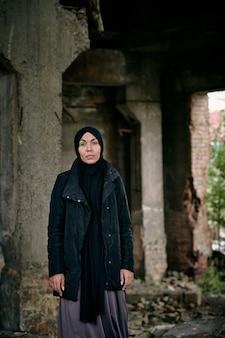 Retrato de uma jovem muçulmana refugiada triste com um hijab e uma jaqueta comprida em pé contra um prédio em ruínas