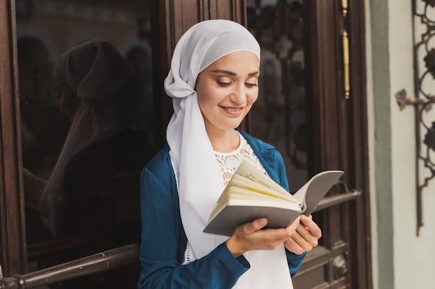 Retrato de uma jovem muçulmana usando hijab lendo um livro ao ar livre