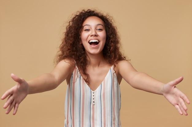 Retrato de uma jovem muito alegre de cabelos castanhos cacheados, mantendo as mãos abertas enquanto olha alegre, isolado em bege