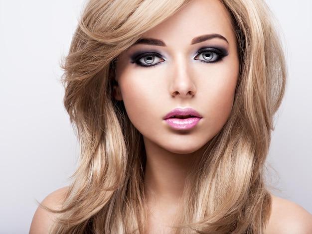 Retrato de uma jovem muito atraente com maquiagem brilhante. lindo cabelo castanho.