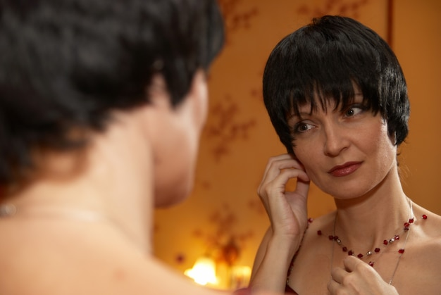 Retrato de uma jovem muito bonita em casa perto de um espelho com reflexo