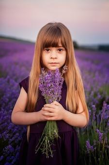 Retrato de uma jovem muito bonita em um vestido violeta com um buquê de lavanda nos raios do sol poente