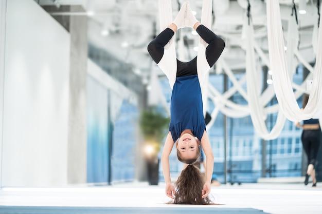 Retrato de uma jovem muito bonita envolvida em yoga mosca em telas.