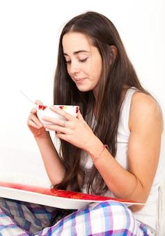 Retrato de uma jovem muito bonita na cama com cabelos castanhos muito compridos que bebe uma tigela de leite