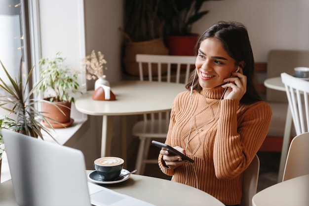 Retrato de uma jovem muito bonita, sentada num café dentro de casa, usando o computador portátil e o celular, ouvindo música com fones de ouvido.