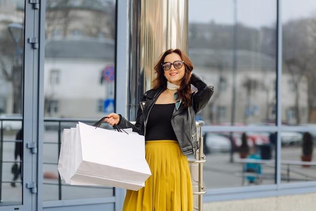 Retrato de uma jovem muito elegante, segurando as sacolas de compras e olhando para a frente de bom humor. compra ideal.