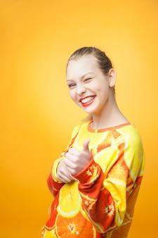 Retrato de uma jovem muito engraçada e sorridente, vestindo um moletom com estampa laranja
