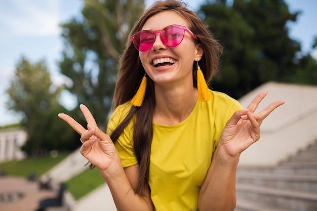 Retrato de uma jovem muito sorridente se divertindo no parque da cidade, positivo, emocional, vestindo blusa amarela, brincos, óculos de sol rosa, tendência da moda no estilo de verão, acessórios elegantes, mostrando o símbolo da paz