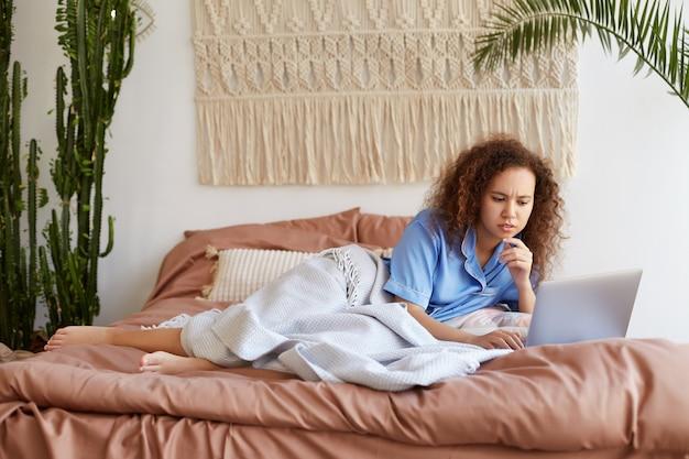 Retrato de uma jovem mulata encaracolada carrancuda deitada na cama, vestida de pijama azul, trabalhando em um laptop, duvidosa, olhando para o monitor e tocando a bochecha.