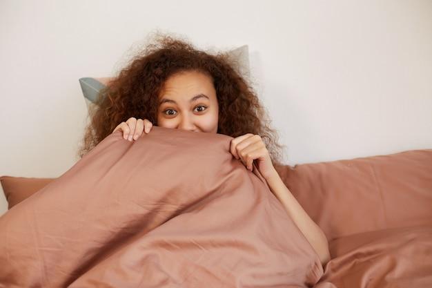 Retrato de uma jovem mulata encaracolada positiva deitada na cama e cobre o rosto com uma manta, com expressão de surpresa e olhos bem abertos.