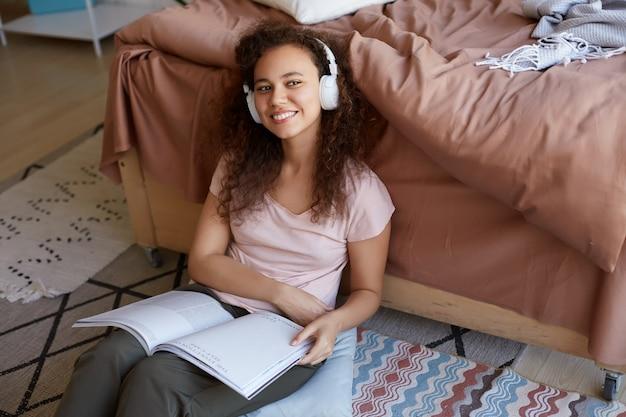 Retrato de uma jovem mulata encaracolada positiva na sala, vestida de pijama, curtindo sua música favorita em fones de ouvido, lendo uma nova revista sobre arte, sorrindo e desvia o olhar.