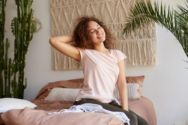 Retrato de uma jovem mulata encaracolada positiva, sentada na cama, vestida de pijama, sorrindo e aproveitando a manhã de domingo.