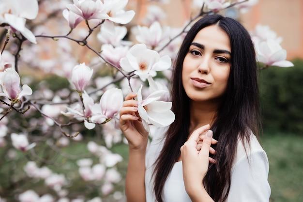 Retrato de uma jovem mulher adorável em flores de primavera flor de magnólia