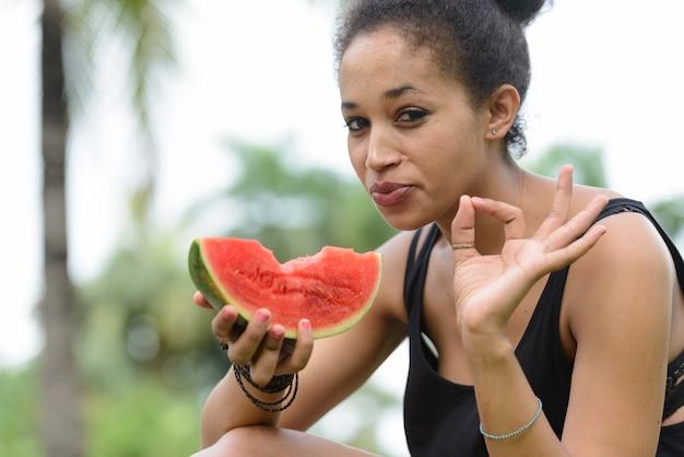 Retrato de uma jovem mulher africana bonita com cabelo afro relaxando no parque ao ar livre
