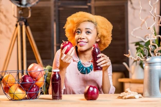 Retrato de uma jovem mulher africana com frutas vermelhas frescas e smoothies, sentado dentro de casa, no aconchegante interior de sua casa