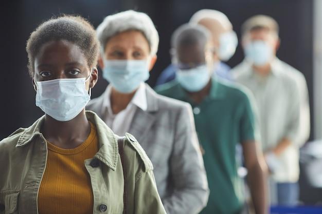 Retrato de uma jovem mulher africana com máscara protetora, olhando em uma fila