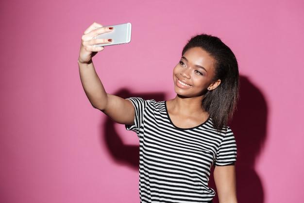 Retrato de uma jovem mulher africana feliz tomando selfie