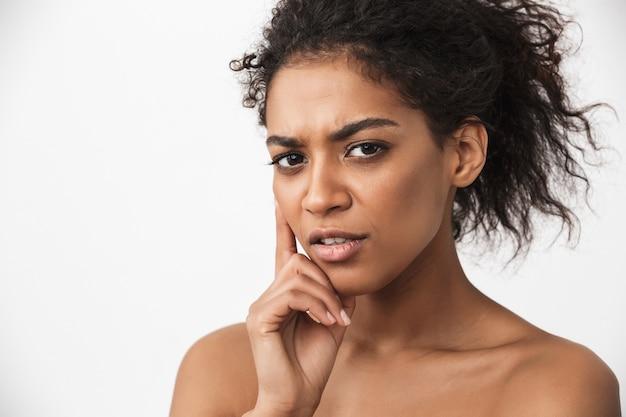 Retrato de uma jovem mulher africana muito séria posando isolado sobre uma parede branca.