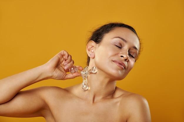 Retrato de uma jovem mulher africana sobre um fundo amarelo, fazendo-se uma massagem do faraó massageador de pescoço.