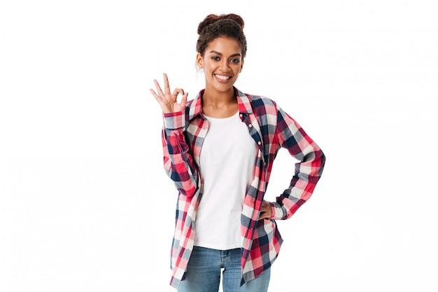 Retrato de uma jovem mulher africana sorridente, mostrando o gesto ok