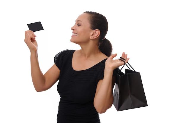 Retrato de uma jovem mulher afro-americana de raça mista, sorrindo com um lindo sorriso cheio de dentes, segurando sacolas de compras e cartão de crédito ou desconto nas mãos, em pé contra um fundo branco com espaço de cópia