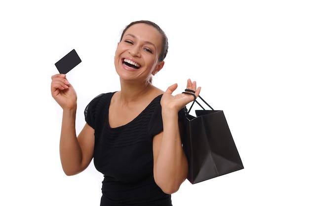 Retrato de uma jovem mulher afro-americana de raça mista, sorrindo com um lindo sorriso cheio de dentes, segurando sacolas de compras e cartão de crédito ou desconto nas mãos, olhando para a câmera em pé contra um fundo branco