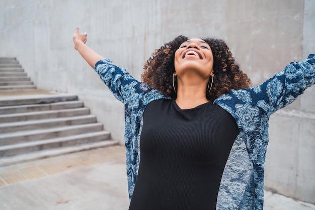 Retrato de uma jovem mulher afro-americana em pé ao ar livre com os braços erguidos e rindo.