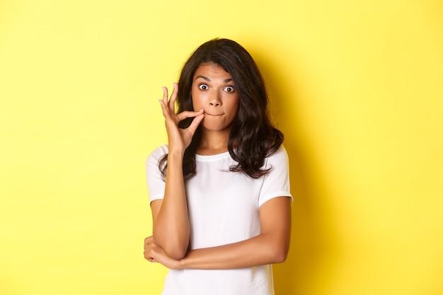 Retrato de uma jovem mulher afro-americana, fazendo promessa de guardar segredo, selar os lábios, fechando a boca com os dedos, em pé sobre um fundo amarelo.