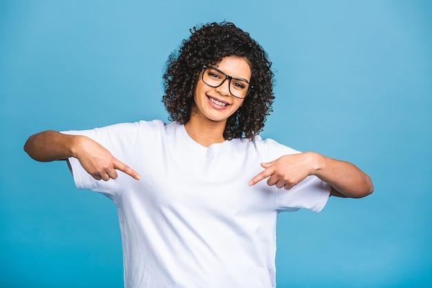 Retrato de uma jovem mulher afro-americana feliz, apontando os dedos para longe, no espaço da cópia isolado sobre o fundo azul.