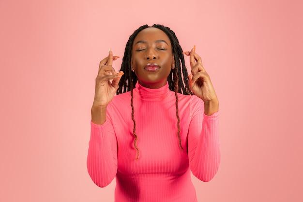 Retrato de uma jovem mulher afro-americana isolada no fundo rosa do estúdio, expressão facial.