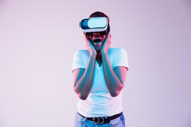 Retrato de uma jovem mulher afro-americana jogando em óculos vr em luz de néon em fundo gradiente. conceito de emoções humanas, expressão facial, dispositivos modernos e tecnologias. fique surpreso.