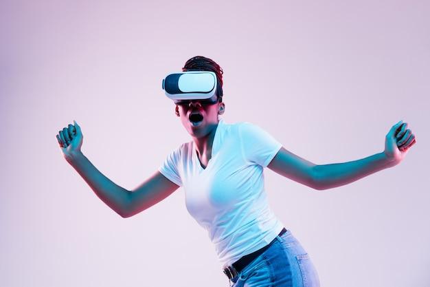 Retrato de uma jovem mulher afro-americana jogando em óculos vr em luz de néon em fundo gradiente. conceito de emoções humanas, expressão facial, dispositivos modernos e tecnologias. fugindo chocado.